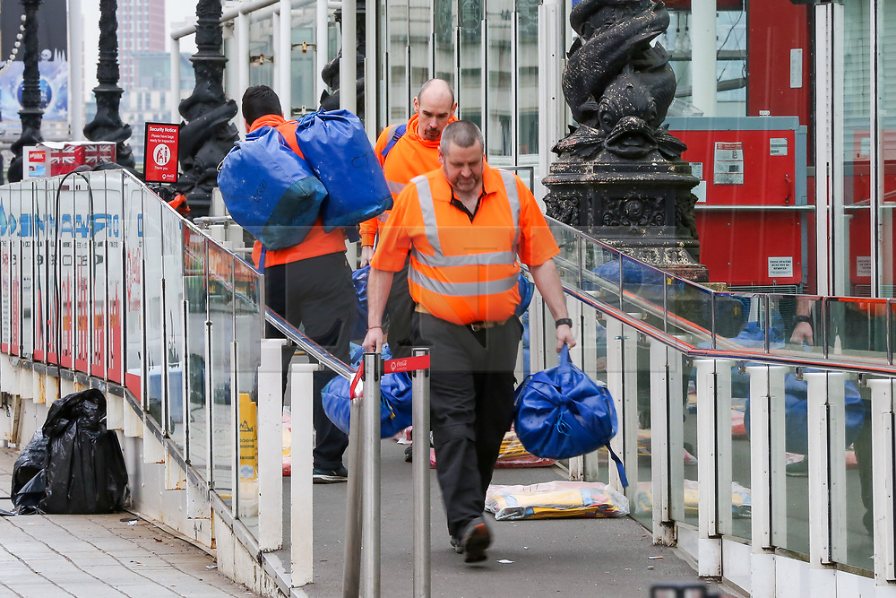 © Licensed to London News Pictures. 07/01/2019. London, UK. Workmen at the entrance of Coca Cola London Eye which is closed for its annual maintenance refurbishment. The popular tourist attraction is 135m/443ft high and there are 32 capsules attached to the wheel will re-open on 23rd January 2019. The London Eye is Europe's tallest cantilevered observation wheel and over 3.75 million visitors visits the London Eye annually. Photo credit: Dinendra Haria/LNP