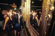 Group of girls standing by gold mirrors, UK clubs, 2000's