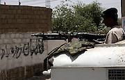 "A Pakistani soldier patrols near graffiti reading: ""Long live the Taliban"" painted on a wall in a minority Christian area near Khuda Ki Basti, Taiser Town in Karachi, Pakistan."