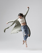 Contemporary and modern dancer, Jennifer Rader, jumping in the studio on a light gray background. Photograph taken in New York City by Rachel Neville.