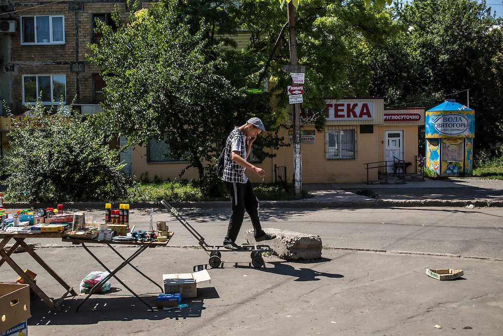 A man talks on the phone while balancing on a cart near a table where he sells small household items in the Oktyabrskaya neighborhood on Sunday, July 27, 2014 in Donetsk, Ukraine.