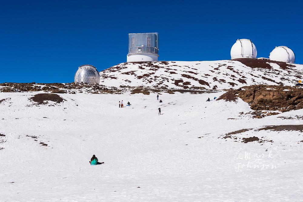 People sledding below the Astronomical Observatories atop Mauna Kea, Big Island (Hawaii Island), Hawaii
