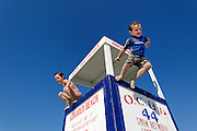 Boy and girl jump from a lifeguard stand at the beach, Ocean City, New Jersey, USA