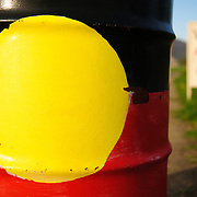 Australian Aboriginal Flag painted on the side of a 44-gallon drum at the Aboriginal Tent Embassy at Old Parliament House in Canberra. The Aboriginal Tent Embassy is a controversial, semi-permanent assemblage claiming to represent the political rights of Australian Aborigines. It is made of a large group of activists, signs, and tents that reside on the lawn of Old Parliament House in Canberra, the Australian capital.