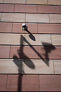 A CCTV camera with the shadow of a traffic camera on the wall of a modern office building in the City of London, the capital's financial district.