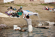 Indian men doing laundry in the waters of The Ganges River at Cabua Pandey Ghat in City of Varanasi, Benares, India