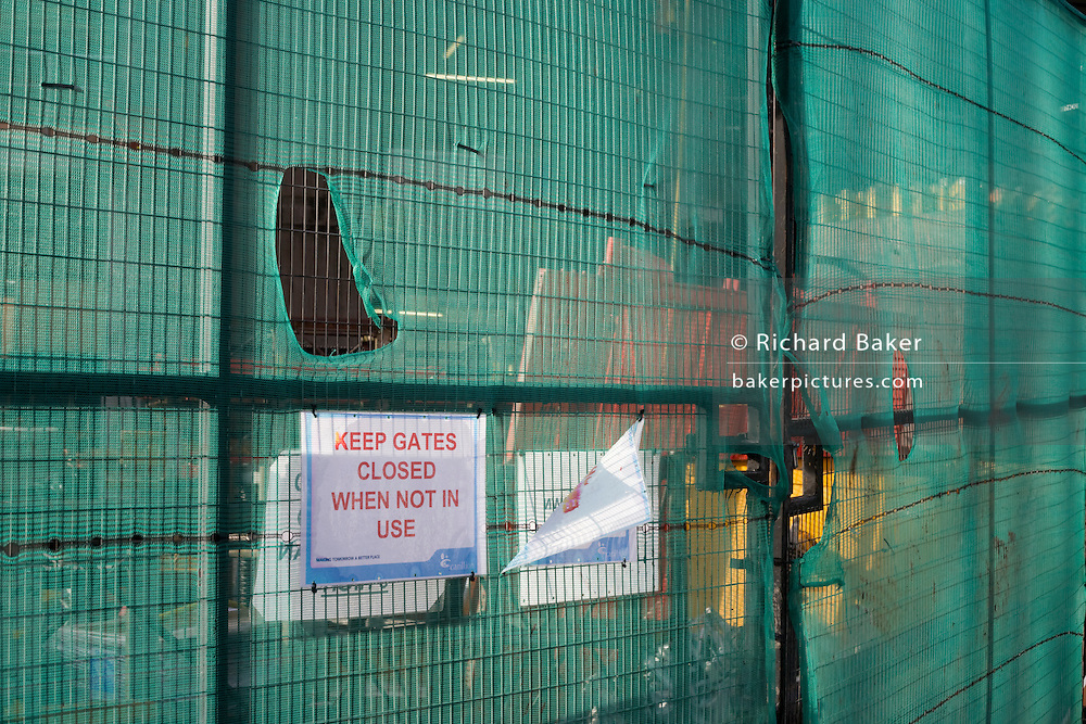 Construction netting with holes and warniong sign at London building site