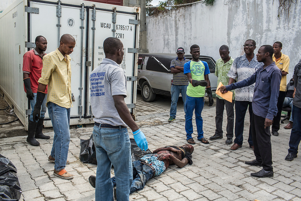 Morgue workers retrieve the body of Jolin Nicolas, 19, who was killed by police while participating an anti-government protest on Wednesday, December 17, 2014 in Port-au-Prince, Haiti.
