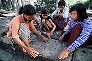 Local children playing a gamve with stones and sticks at Angkor Wat, Siem Reap, Cambodia. The temples at Angkor are spread out over some 40 miles around the village of Siem Reap, about 192 miles from the Cambodian capital, Phnom Penh. They were built between the eighth and 13th centuries and range from single towers made of bricks to vast stone temple complexes. Regarded as the supreme masterpiece of Khmer architecture, it is a huge pyramid temple built by Suryavarman II between 1113 and 1150. It is surrounded by a moat 570 feet wide and about four miles long. The bas-relief carvings are of the highest quality and the most beautifully executed in Angkor..