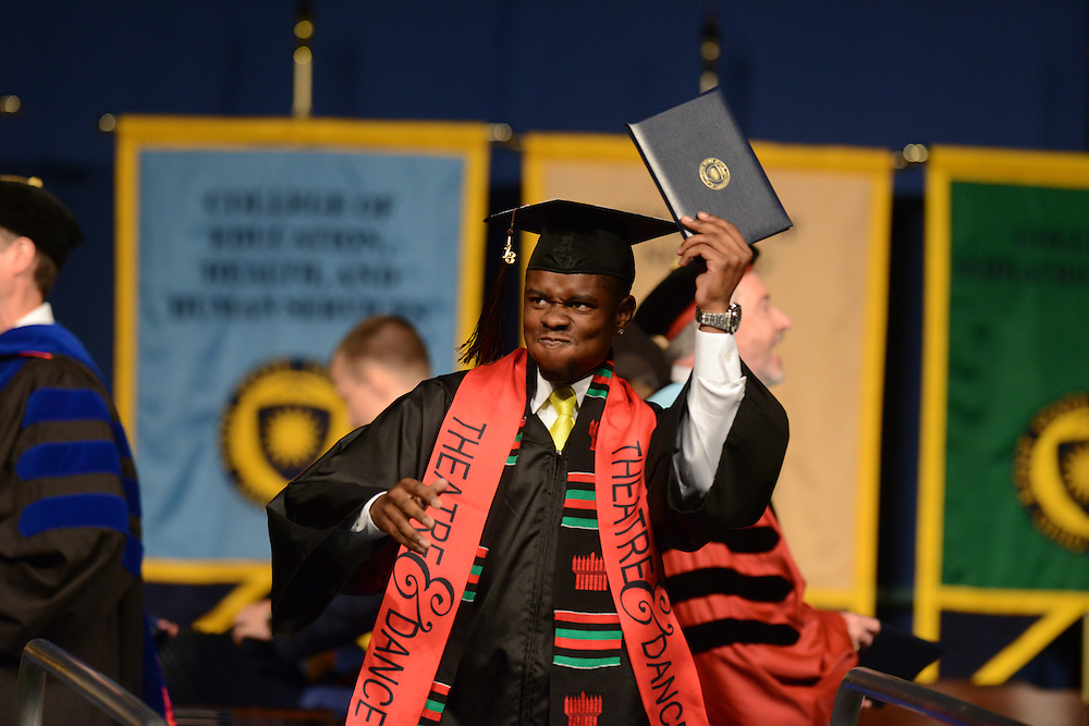 A graduate of the College of the Arts shows his enthusiasm while getting his diploma during the Spring, 2013 Commencement.