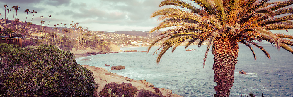 Laguna Beach California retro panorama photo with palm trees, Pacific Ocean, and the Orange County Southern California coastline.
