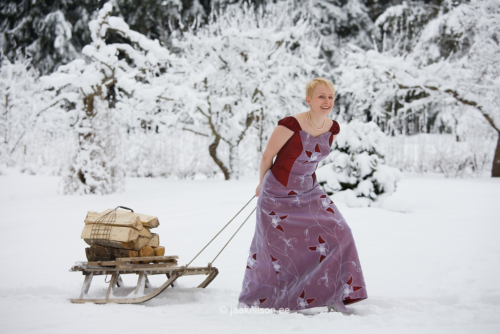 Young Woman in Wedding Dress Pulling Wooden Sledge with Firewoods in Winter.