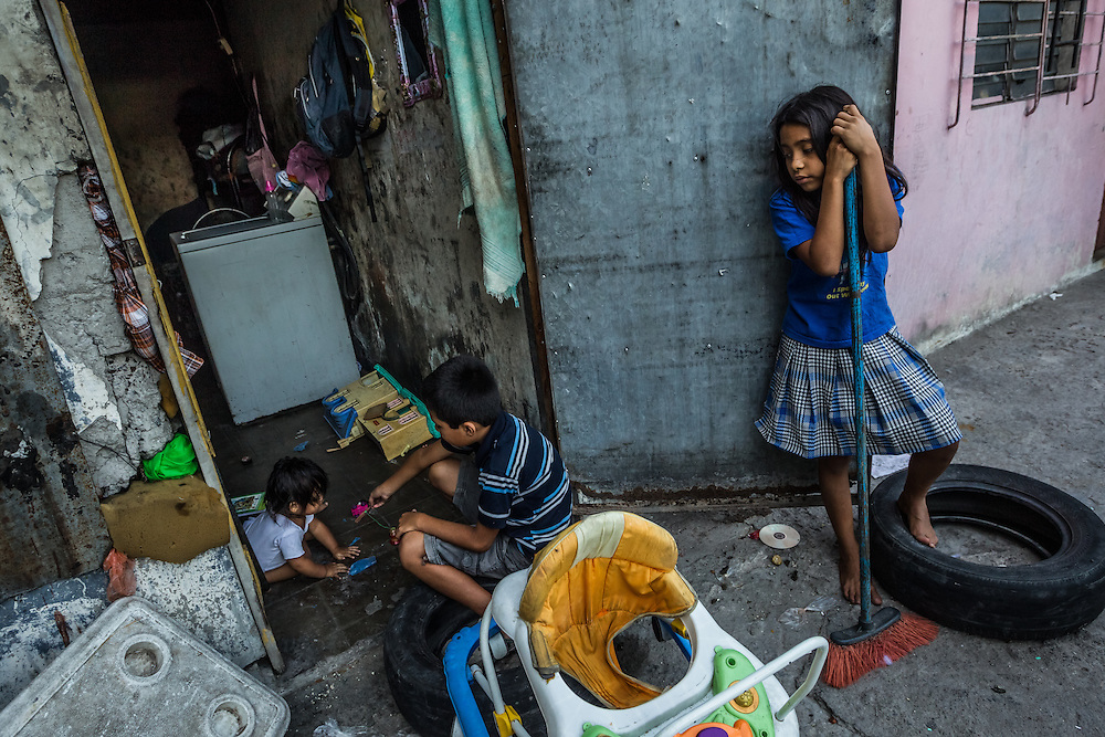 SAN SALVADOR, EL SALVADOR - MAY 25, 2015:  Maria de los Angeles Ramirez, 10, (right) takes care of her baby sister, Sophia Alejandra Ramirez, 10 months, while her parents work. The government argues that the gang crackdown is just part of a broader strategy to invest in education and job creation in the most violent communities, rehabilitate gang members, and strengthen the rule of law.  The strategy's road map is an ambitious $2.1 billion plan developed with the help of the private sector, churches and aid groups.  But El Salvador's limping economy cannot create the jobs that are needed to provide an alternative to the gangs.  Growth has hovered around 2 percent for years. Remittances from Salvadorans working in the United States account for about 17 percent of national income and half the workforce toils in the informal economy.  PHOTO: Meridith Kohut for The New York Times
