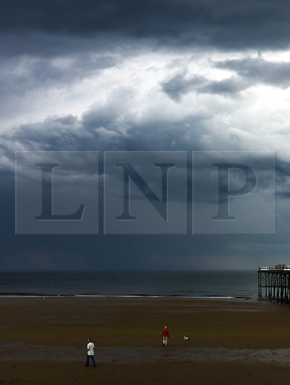 © Licensed to London News Pictures. <br /> 08/06/2014. <br /> <br /> Saltburn, United Kingdom<br /> <br /> A couple walk their dog on the beach as dark and brooding thunder clouds form over Saltburn, Cleveland.<br /> <br /> Photo credit : Ian Forsyth/LNP