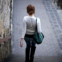 A slim young woman dressed casually walking down steps