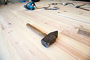 a large heavy hammer being used for installing a solid wood parquet flooring