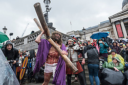 """© Licensed to London News Pictures. 30/03/2018. LONDON, UK.  Jesus, played by James Burke-Dunsmore, carries his cross en route to his crucifixion. The Wintershall Players present their traditional """"The Passion of Jesus"""" play in Trafalgar Square on Good Friday in front of large crowds despite the heavy rain.  The play brings to life the events leading to the crucifixion of Jesus Christ, played by James Burke-Dunsmore, and his subsequent resurrection.  Photo credit: Stephen Chung/LNP"""