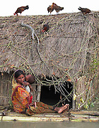 Bewilder Momina Biwi sits near her inundated hut by floodwaters and carries her little son at Phulbari village, about 337 kilometers southwest of Gauhati, the capital city of Northeastern Indian state, Assam, Wednesday, June 30, 2004..Floodwaters of the Asia'a one of the largest river, Brahmaputra and its 35 tributaries have affected more than one million in all of Indian subcontinent and disrupted communication in many parts of the India and Bangladesh, sources said. (AP Photo/ Shib Shankar Chatterjee).
