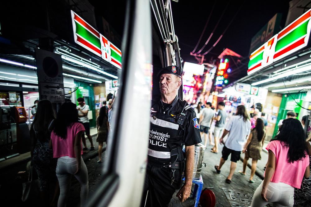David Eke, a member of the Foreign Tourist Police, takes a small break in a police van amidst the neon lights of Walking Street in Pattaya, Thailand.