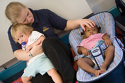 Nursery Nurse comforting a toddler and a baby,
