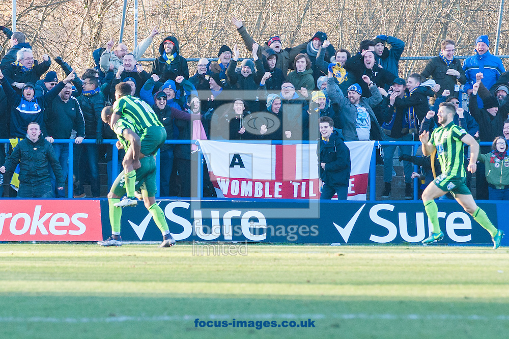 Tom Elliott of AFC Wimbledon celebrates as Dominic Poleon jumps on him after scoring a dramatic injury time winner during the FA Cup match at Tameside Stadium, Ashton-under-Lyne<br /> Picture by Matt Wilkinson/Focus Images Ltd 07814 960751<br /> 04/12/2016