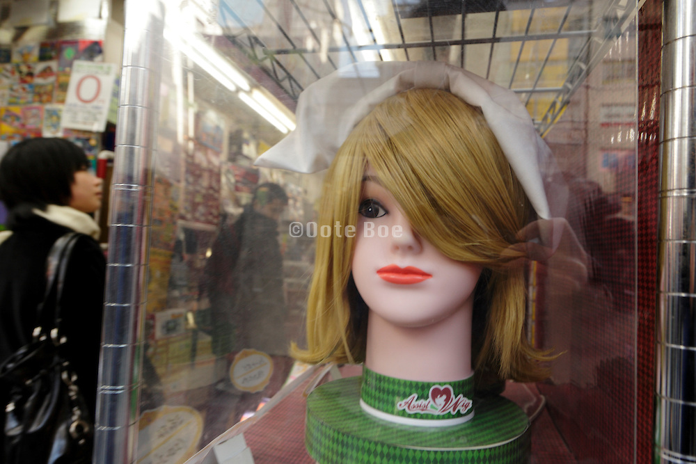 blond haired wig displayed in window of a Akihabara shop Tokyo Japan