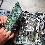 Electronic waste export to Nigeria...Alaba International Market, one of the largest markets for electronic goods in West Africa.  New and old - and a lot of non-working electronic goods such as TVs and computers come in to the market via Lagos harbour from the US, Western Europe and China..Osta Anyche, a TV repair man at Alaba Market.  His speciality is Sony, Panasonic and Philips televisons..The shipment - TV-set originally delivered to municipality-run collecting point in UK for discarded electronic products - was tracked and monitored by Greenpeace using a combination of GPS (Global Positioning System using satellites), GSM (positioning using data from mobile networks to triangulate approximate positions) and an onboard radiofrequency transmitter (used for making triangulations in combination with handheld directional receivers used by team on ground) is placed inside the TV-set.  The TV arrived in Lagos in container no 4629416.
