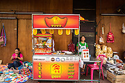 17 OCTOBER 2012 - BANGKOK, THAILAND:    A snack vendor's cart is decorated with Vegetarian Festival banners, showing she is selling vegan snacks during the Vegetarian Festival in Bangkok. The Vegetarian Festival is celebrated throughout Thailand. It is the Thai version of the The Nine Emperor Gods Festival, a nine-day Taoist celebration celebrated in the 9th lunar month of the Chinese calendar. For nine days, those who are participating in the festival dress all in white and abstain from eating meat, poultry, seafood, and dairy products. Vendors and proprietors of restaurants indicate that vegetarian food is for sale at their establishments by putting a yellow flag out with Thai characters for meatless written on it in red.      PHOTO BY JACK KURTZ