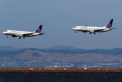 Embraer ERJ-175LR (N160SY) operated by SkyWest Airlines for United Express and Boeing 737-824 (N77520) operated by United Airlines landing at San Francisco International Airport (KSFO), San Francisco, California, United States of America