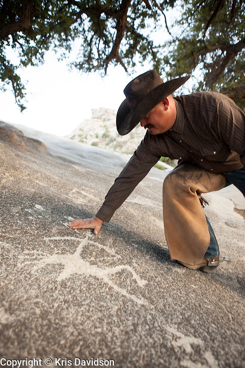 """Rancher (or """"cowpuncher"""" as he prefers to be called) Drayson Harris surveys the modern petroglyphs at the Indian Bread Rocks Picnic Area in Cochise County, Arizona. Indian Bread Rocks Picnic Area is administered by the Bureau of Land Management, Safford Field Office -- it is situated in the midst of Drayson Harris's ranch land. Many uses occur in this beautiful setting located south of Bowie, Arizona.  The surrounding mountains provide picnickers, hikers and hunters with a glorious view of the unique rock formations in the mountains. There is plenty of evidence among the boulders that Apaches and other native peoples once lived and hunted here. The rock art on the slabs near the picnic tables are modern petroglyphs (likely created after the Apache were forced off the land)."""