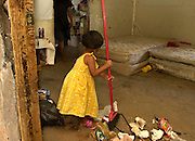 A 4-year-old girl sweeps the floor of her home on the Tohono O'odham Reservation, Arizona, USA.  Daughter of a recovering addict, the girl was born with cocaine in her system.