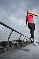 Woman jogging on foot bridge low angle view Millennium Bridge London England