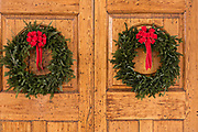 The wooden doorway of a historic home decorated with a Christmas wreaths on Meeting Street in Charleston, SC.