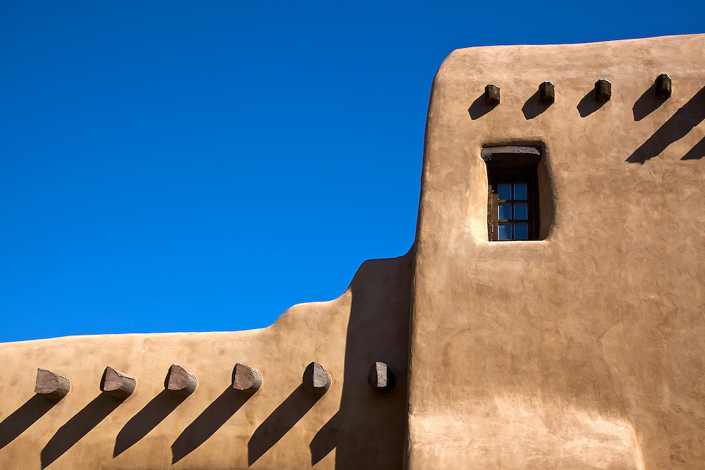 Azure blue sky and rich Adobe textures color this iconic Southwest scene in Santa Fe, New Mexico.