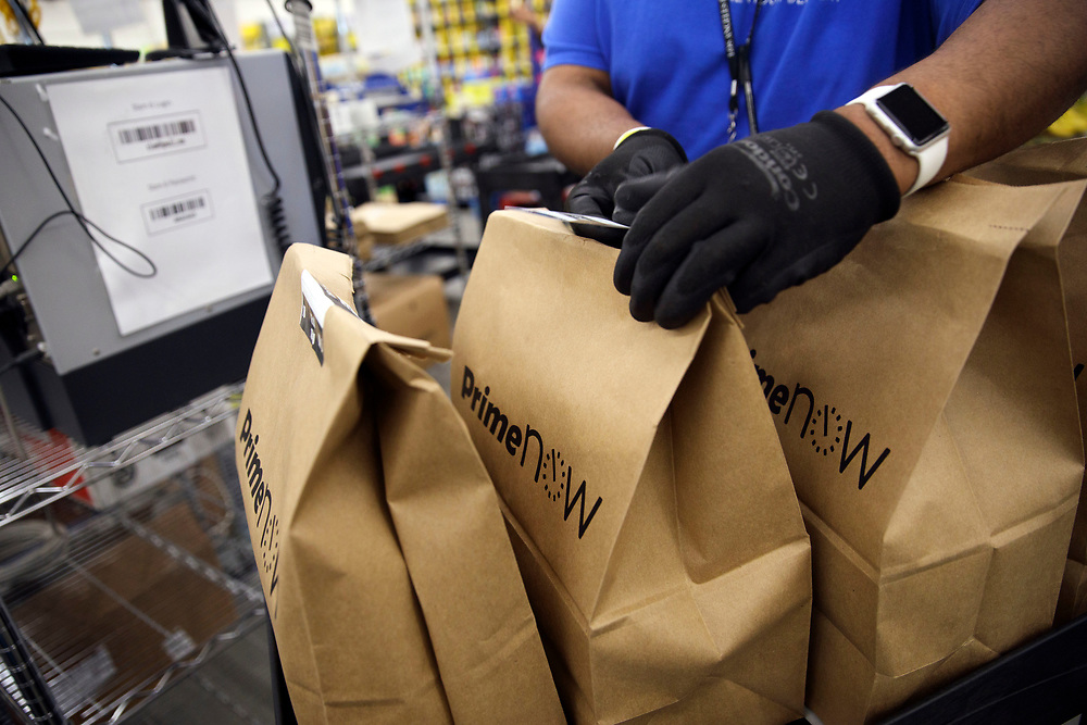 An Amazon associate fills shopping bags with products for customers orders at the Amazon.com Inc. Prime Now fulfillment center warehouse on Monday, March 27, 2017 in Los Angeles, Calif. The warehouse can fulfill one and two hour delivery to customers. Complex supply chains such as Amazon's and e-commerce trends will impact city infrastructure and how things move through cities. © 2017 Patrick T. Fallon