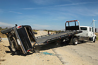Man preparing to lift crashed car onto tow truck