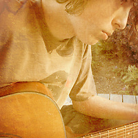 Young male thoughtfully playing acoustic instrument
