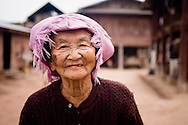 Laos, a small village near Muang Sing in the northern part of the country. Elderly Tai Lu woman with her house at the background.