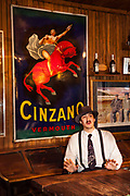 Waiter under old Cinzano sign wears Carlos Gardel tie, Ramos Generales cafe dates back to Salamon family 1906, Ushuaia, Argentina.