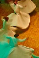 """Turquie. Anatolie Centrale. Ville de Konya. Le grand maitre soufi Djalal ed-Din Rumi ou Djalal-e-Din Mohammad Molavi Rumi ou Djalaleddine Roumi (1207-1273), fondateur de l'Äôordre des derviches tourneurs est connu sous le nom de Mevlana. Il est enterré à Konya. Le Sema est une danse sacrée des derviches tourneurs soufis qui s'execute dans le semahane (salle de danse).Le derviche est vetu d'une longue tunique blanche, couleur du deuil, et d'une toque cylindrique en poil de chameau, symbole de la pierre tombale. La main droite levee vers le ciel, il recueille la grace divine qu'il transmet à  la terre par la main gauche tournée vers le sol. Il pivote sur le pied gauche en tracant un cercle au tour de la piste pour parvenir à l'extase qui lui permet de s'unir à Dieu. La danse est donc une priere, un depassement de soi et l'union supreme avec Dieu. Le cercle est egalement le symbole de la Loi religieuse qui embrasse la communaute musulmane toute entiere et ses rayons symbolisent les chemins menant au centre ou se trouve la verite supreme, le dieu unique qui est l'essence meme de l'Islam. Chaque annee pour l'anniversaire de la mort de Mevlana les derviches se retrouvent a Konya pour une ceremonie. // Turkey. Central Anatolia. City of Konya. The sufi master Djalal ed-Din Rumi ou Djalal-e-Din Mohammad Molavi Rumi ou Djalaleddine Roumi (1207-1273), founded of whirling dervishes order is knows with the name of Mavlana. Is bury in Konya. Sema or sama is a term that means hearing in Arabic and Persian. It is used to refer to some of the ceremonies used by various sufi orders and often involves prayer, song, dance, and other ritualistic activities. Sema dancing is known to Europeans as the dance of the Whirling Dervishes or """"Sufi whirling"""", although many forms of sema do not include whirling. In the Mevlani sufi tradition, sema represents a mystical journey of spiritual ascent through mind and love to """"Perfect."""" In this journey the"""