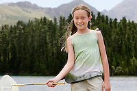 Girl (7-9) standing outdoors by lake holding butterfly net front view portrait.