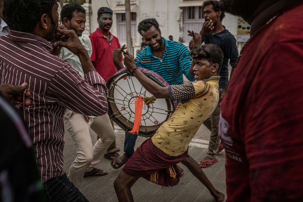 Local man sweats as he provide percussion for a procession of Lord Ganesha statues on the back of trucks along Beach Road and the waterfront during the Ganesh Chaturthi Festival.  Pondicherry, India.
