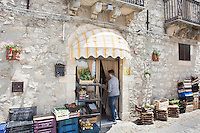 GANGI, ITALY - 30 MAY 2015: A fruit vendor is here in the historical center of Gangi, Italy, on May 30th 2015. Gangi is a town with a population of 7,000 between Palermo and Catania, in the centre of Sicily, whose local administration is giving away abandoned houses of the historical centre for free. The Mayor of Gangi Giuseppe Ferrarello conceived the initiative of giving houses for free as a means to diversify the local economy - primarily dependent on agriculture and animal husbandry - by boosting tourism-related activities, and consequently counteract the phenomenon of depopulation that is typical of many small Italian towns where employment possibilities have been on a downward trajectory for years. The renovations of the assigned homes have also given work to local artisans.