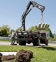 """With the use of his crane Stephen Green swings his 2000 lb granite sculpture """"Advantage"""" into position at Hesky Park on Tuesday afternoon as the second installation for the Greater Meredith Program's Sculpture Walk.   (Karen Bobotas/for the Laconia Daily Sun)"""