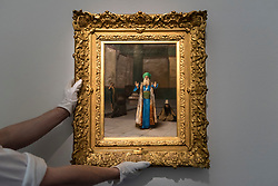 "© Licensed to London News Pictures. 20/04/2018. LONDON, UK. A technician presents ""A Sultan at Prayer"" by Jean-Léon Gérôme (Est. 200-300k) at a preview of works in Sotheby's 20th Century Middle East, Orientalist and Islamic upcoming art sales in New Bond Street.  The works will be sold at auction in the last week of April.    Photo credit: Stephen Chung/LNP"