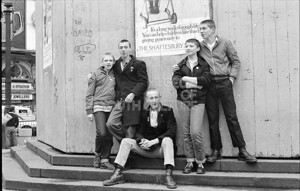 Group of skins on steps, Piccadilly Circus, London. 1980s.