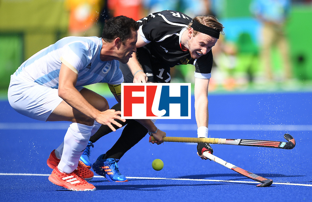 Argentina's Pedro Ibarra (L) firhgts for the ball with Germany's Christopher Ruhr during the men's field hockey Argentina vs Germany match of the Rio 2016 Olympics Games at the Olympic Hockey Centre in Rio de Janeiro on August, 11 2016. / AFP / MANAN VATSYAYANA        (Photo credit should read MANAN VATSYAYANA/AFP/Getty Images)