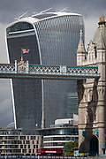 As a London bus crosses the Thames river, the British Union Jack flag flies from the upper gantry of Victorian-era Tower Bridge, near the modern Walkie Talkie building (aka 20 Fenchurch Street), on 14th September 2017, in London, England.