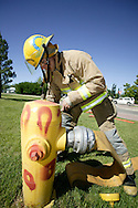 © 2008 Randy Vanderveen, all rights reserved.Grande Prairie, Alberta.Firefighter Todd Russell catches a hydrant as Grande Prairie firefighters train in Muskoseepi Park by conducting some Performance Standard Drills during the mid-day hours of a summer day.