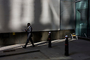 A black gentleman walks past an empty seat in a sunlit corner of a City of London lane.